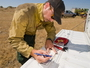 Photo of Dustin Smith takes field weather observations during a 2010 prescribed burn in Idaho.