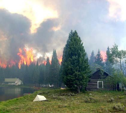 A forest fire burns behind cabins along Lost Lake.
