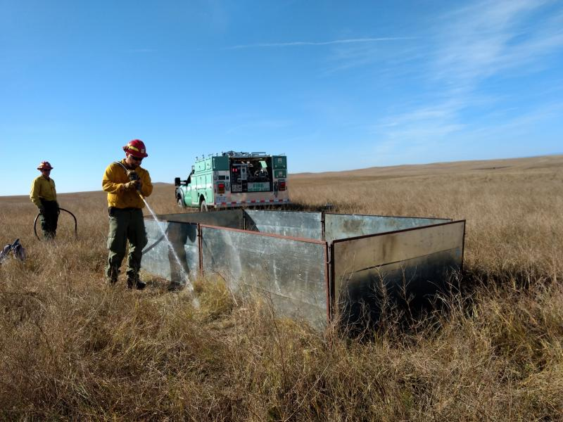 A fire crew creates a wetline around a burn box to help keep a fire controlled.