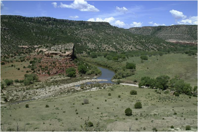 A photo of a grassland dotted with juniper. A river runs through it, curving to the left around a rock formation sitting on a red dirt plateau.