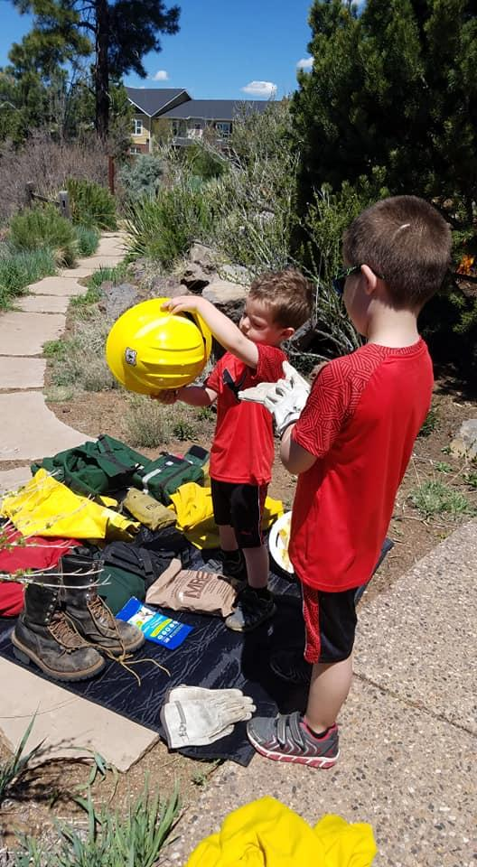 Two boys check out hard hats, boots, and other firefighting equipment on a stone path.