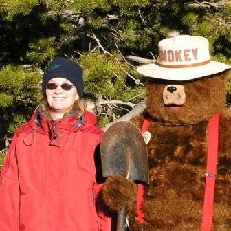 A photo of Paula Fornwalt standing with Smokey Bear