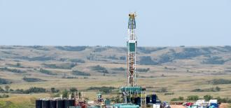 A horizontal rig for drilling and hydraulic fracturing is surrounded by trucks and equipment in a grassy field. Grassy hills rise up behind it.