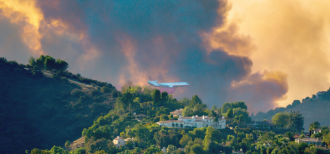 A DC10 Air Tanker is seen over the Woolsey Fire in California
