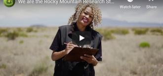 "Screenshot of the thumbnail for the ""We are the Rocky Mountain Research Station"" video, including an image of a smiling woman standing in a field holding a clipboard."