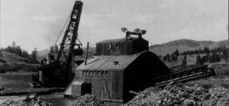 A photo of a structures used at a gold mine, black and white photo taken in 1936. Piles of rocks in the foreground demonstrate the rocky landscape, showing the negative ecological effects scientists face today in attempts to restore abandoned mines