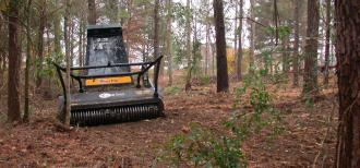 The photo shows a tractor-like machine used for mastication. It is located in a forest