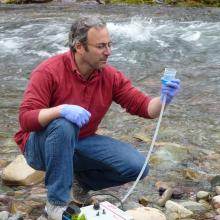 Mike Schwartz crouching in a stream with eDNA sampling equipment.