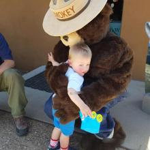 A child hugging Smokey Bear at a Science Saturday fire awareness event celebrating National Fire Preparedness Day.