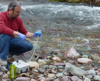 A researcher in a stream with eDNA sampling equipment.