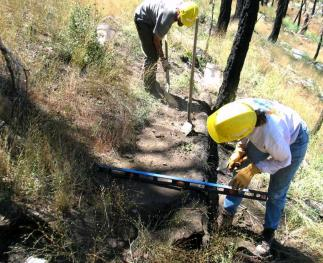 Researchers determining the effectiveness of erosion mitigation measures on a hiking trail.