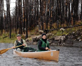 A man and woman in a canoe on a river, smiling at the camera, with trees in the background.