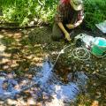 A researcher crouches near a stream with eDNA sampling equipment.
