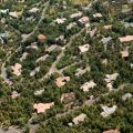 The photo shows a suburban neighborhood interwoven with trees.