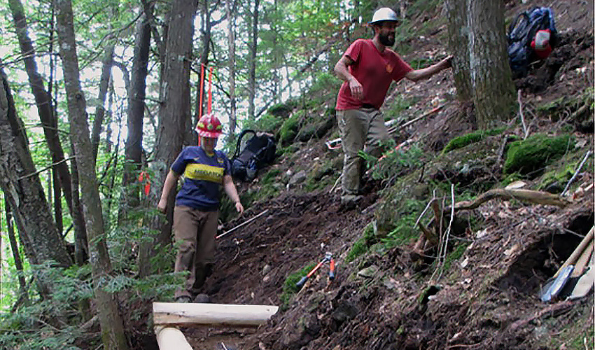 Two workers performing trail maintenance