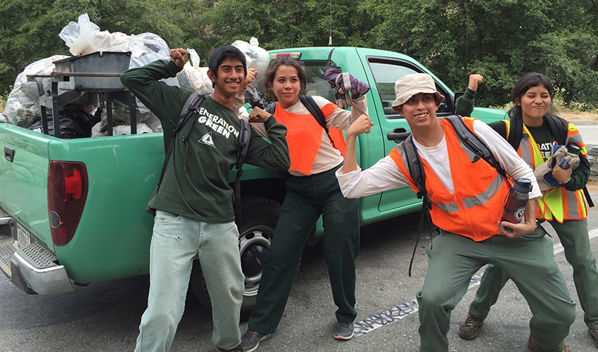 Trail crew posing in front of a Forest Service vehicle
