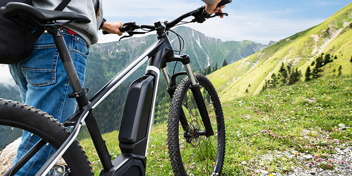 A picture of an e-Bike on top of a mountain trail near a high country meadow area.