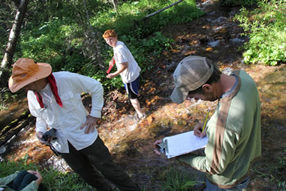 A student and two field instructors with the Youth Forest Monitoring Program measure rocks, and monitor temperatures in a stream near Webb Lake in the Scapegoat Wilderness.