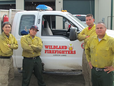 A photo of Leech Lake Wildland Fire crew members standing in front of a truck.
