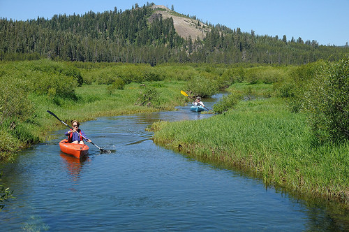 Two kayakers row down an engorged creek through Van Norden Meadow in Royal Gorge.