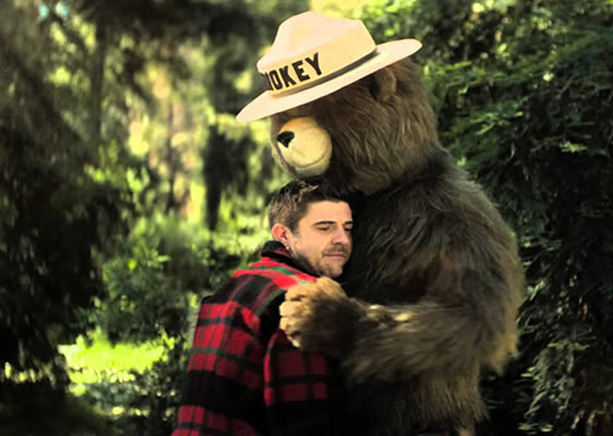 A photo showing Smokey hugging someone after they did a good deed that prevented a wildfire.