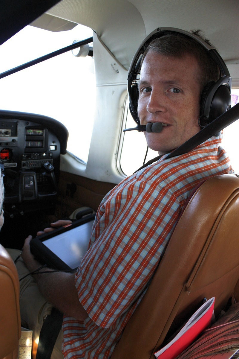 A picture of Ryan Hanavan in the right seat of a small aircraft wearing a headset.