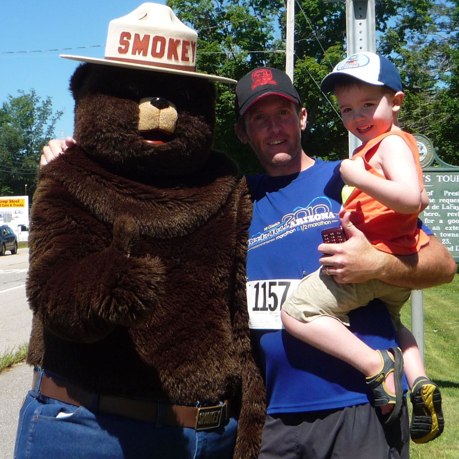 A picture of Ryan Hanavan holding his son in his arms, standing next to Smokey Bear.
