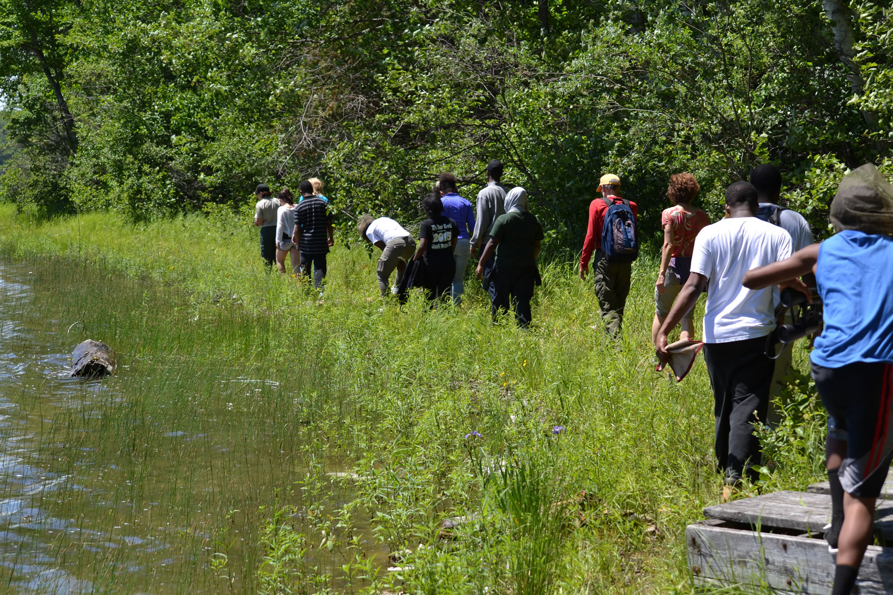 A group of young people from Detroit walk a somewhat unfamiliar path along the shoreline of Clear Lake on the Hiawatha National Forest in Michigan.