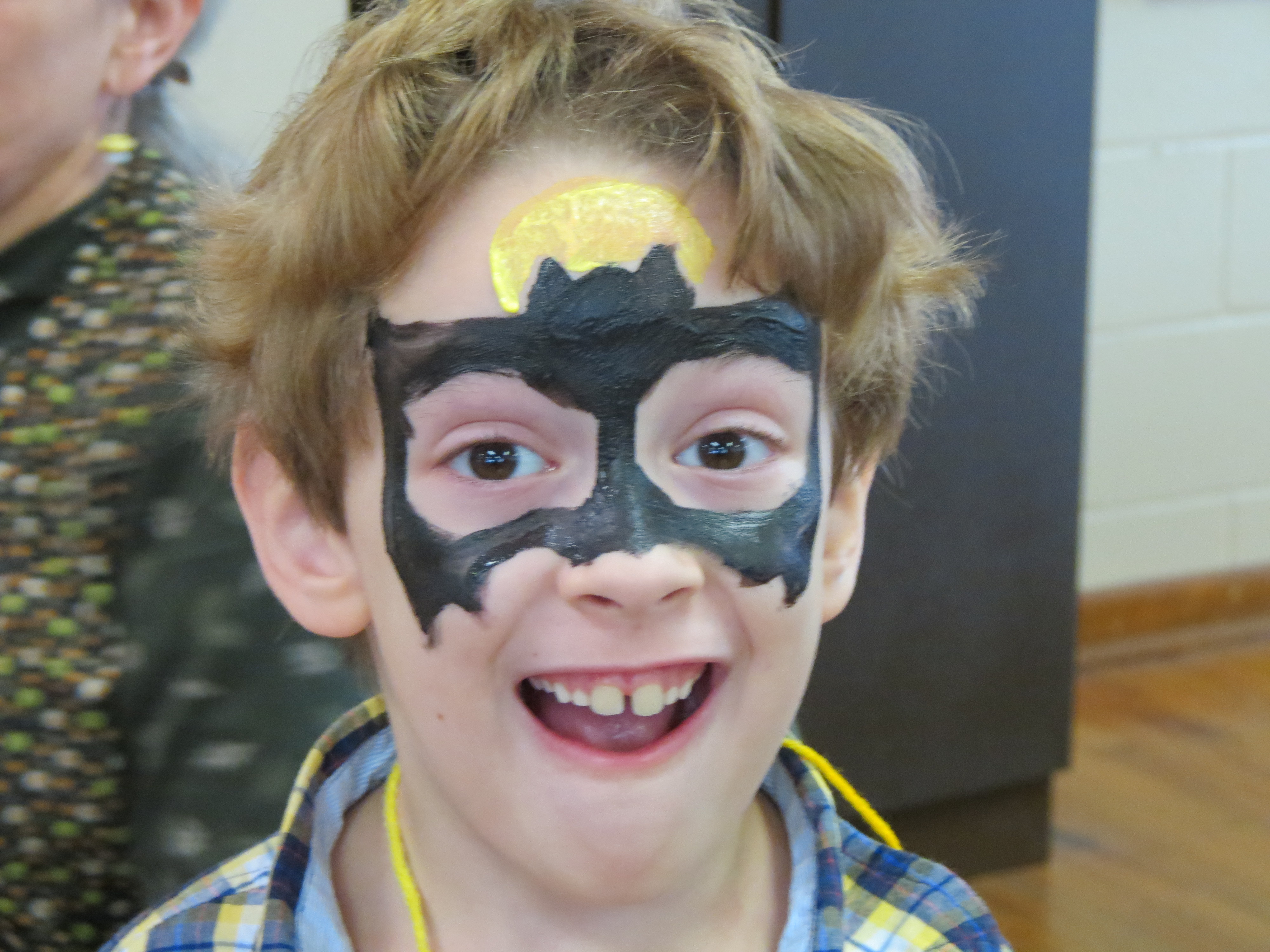 A photo of a young visitor with his face painted as a bat