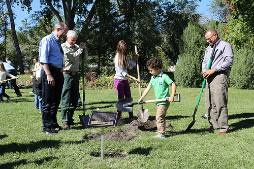 A photo of Mike Wingfield, U.S. Forest Service Chief Tom Tidwell, and Jim Reaves, watch as two children prepare to plant a tree.