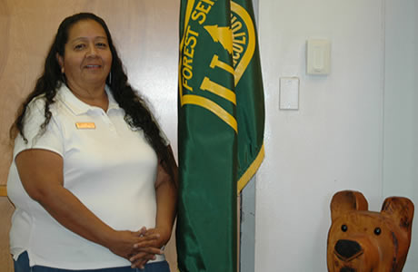 Faces of the Forest Angelita Bulletts posing with the Forest Service flag