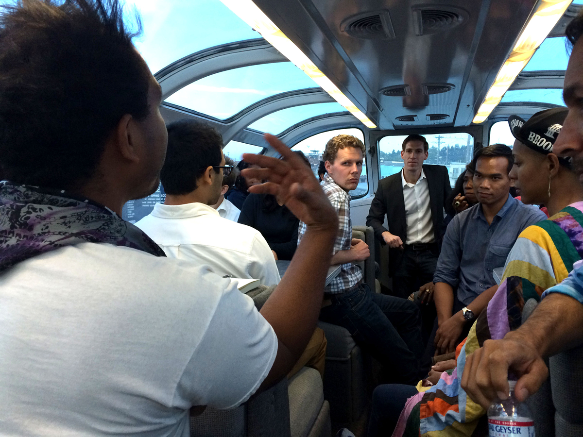 Participants in the Millennial Trains Project enjoy an onboard mentoring session and huddled around listening to a speaker while onboard a train.