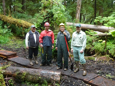 A photo of Tribal Liaison Donald Frank, Angoon Trail Crew Leader Aaron McCluskey, Youth Conservation Corps member Roger Williams, also an Angoon tribal member, and Admiralty Island National Monument Ranger Chad VanOrmer