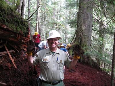 A photo of trails specialist Tom Davis holding up his dirty work gloves.