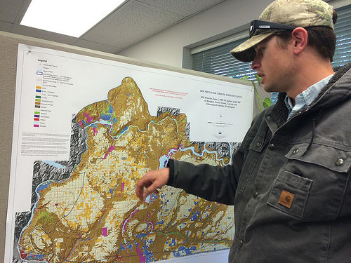 A photo of Michael Brown showing key places on a map where he and others work with ranchers.