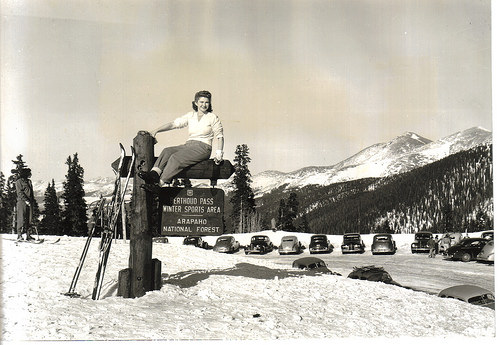 A photo of a woman posing atop a U.S. Forest Service sign after 5 feet of snow
