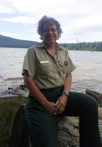 Nancy Lankford poses for a photo on the shoreline of Timothy Lake with Mt. Hood in the background. (Photo courtesy of the U.S. Forest Service)