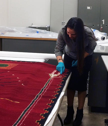 "A photo of Nanebah Nez examing the intricate weaving of ""Sandpainting of the Arrow People,"" a 13-foot-by-12-foot hand-woven Navajo rug that took her great great-grandmother Bahe Shondee years to make."