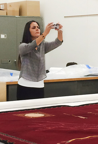 A photo of Nanebah Nez taking a photograph of the massive hand-woven Navajo rug her great-great-grandmother made for an Arizona trading company.