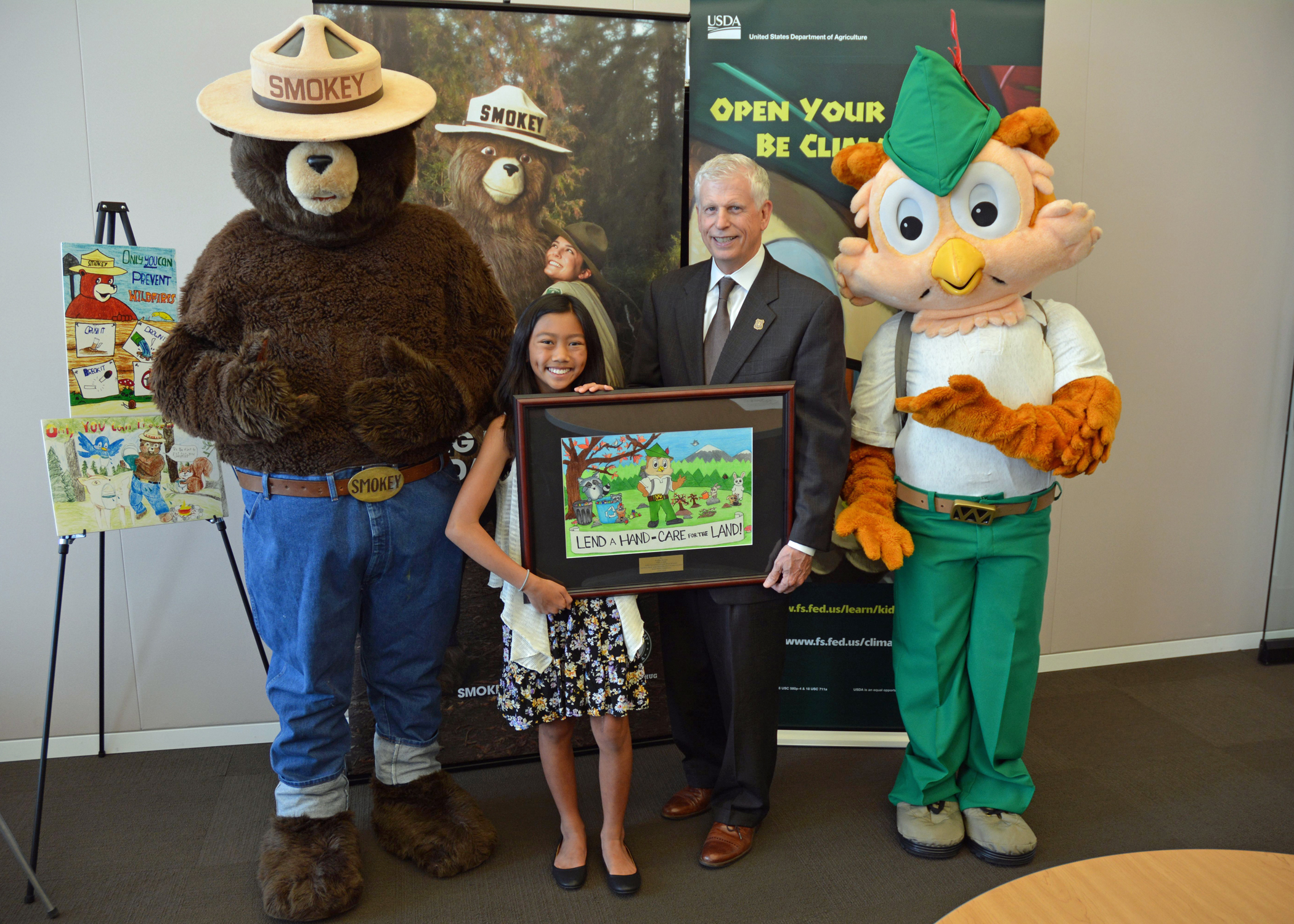 Audrey Morga, national winner of the 2015 National Smokey Bear and Woodsy Owl poster, stands with U.S. Forest Service Chief Tom Tidwell, Smokey Bear and Woodsy Owl. (Photo by Dominic Cumberland, U.S. Forest Service)