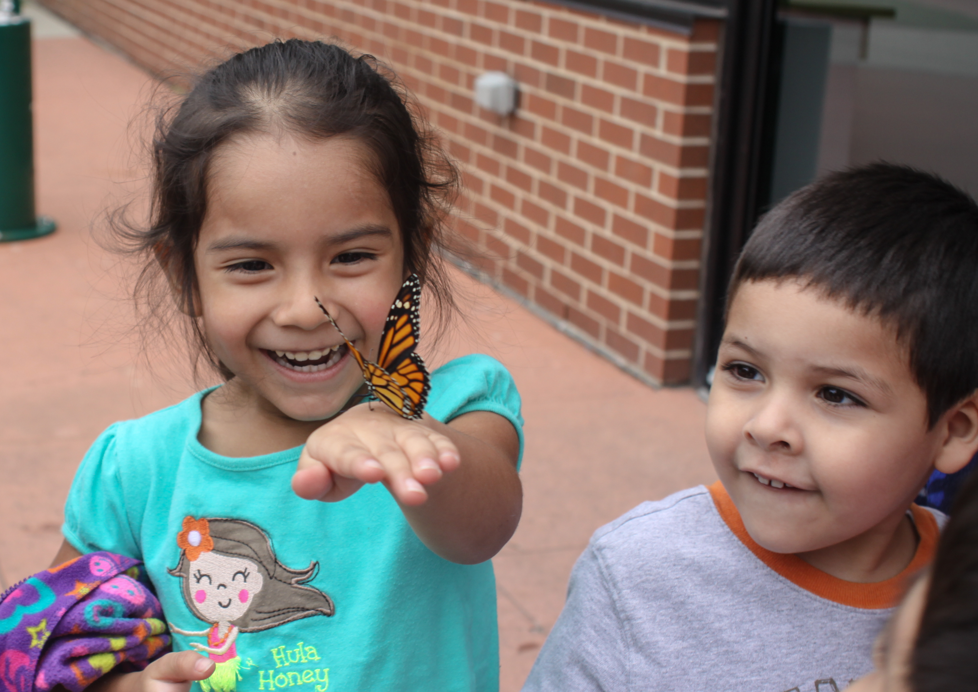 Children enjoy a Monarch Butterfly during a community event in Chicago. (Photo by Alexander Rivera for El Valor)