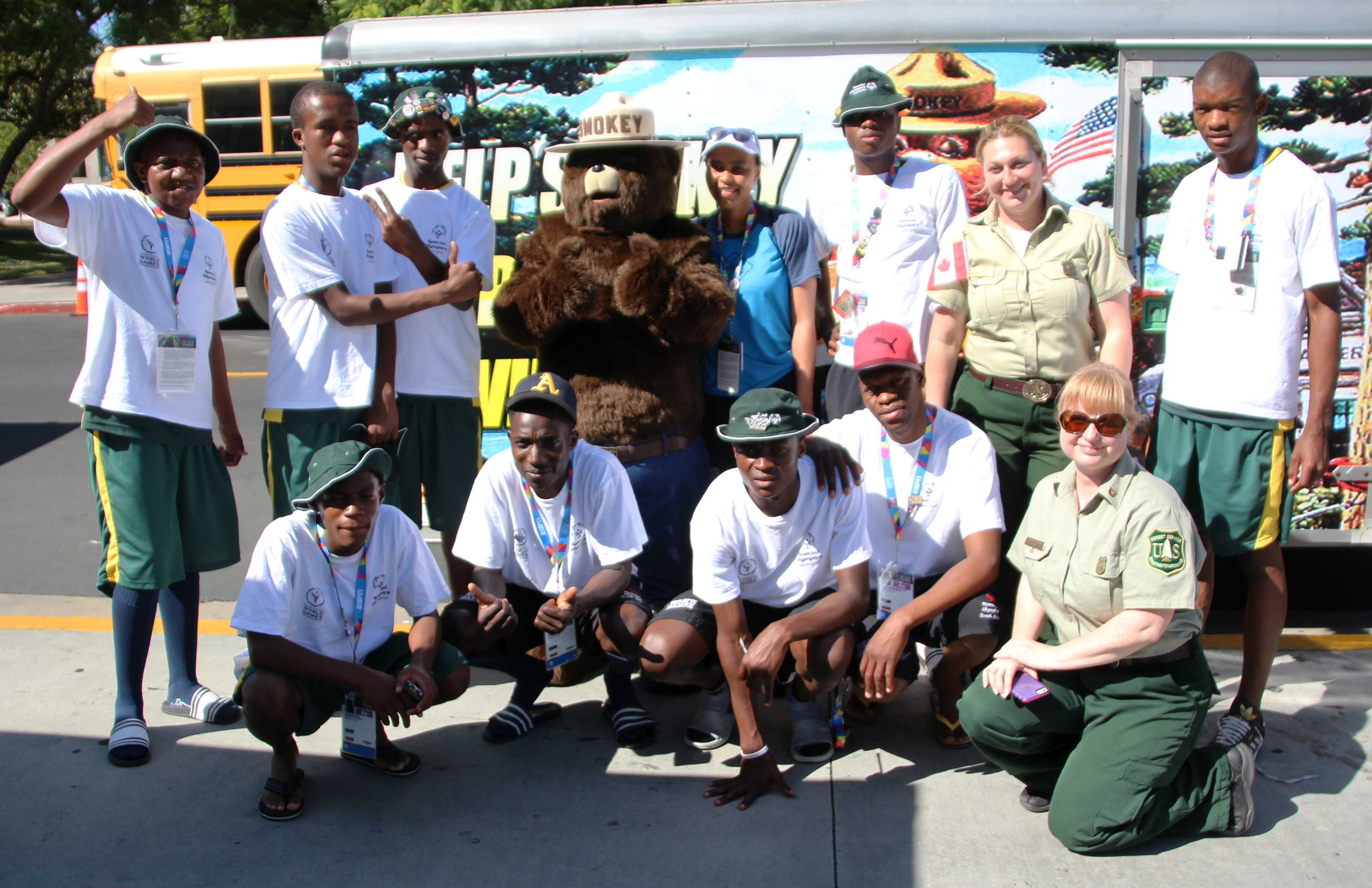 Smokey Bear and U.S. Forest Service employees pose for a picture with the South African team at the World Special Olympics in Los Angeles.
