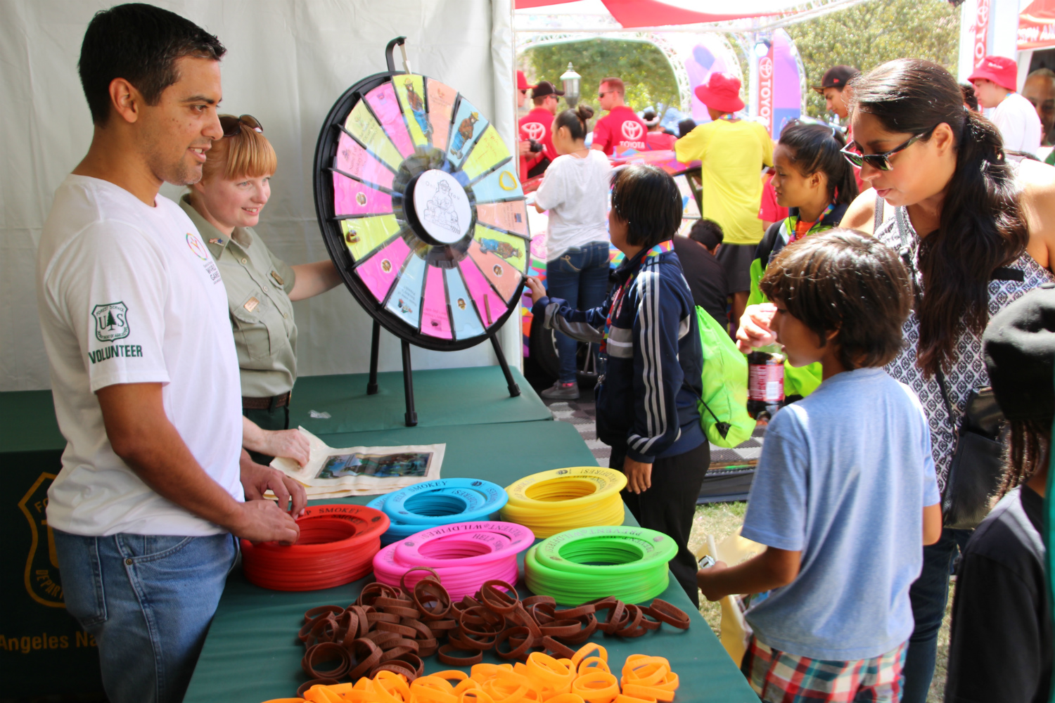 Jose Henriquez-Santos (left), a landscape architect, and Joanna Huckabee (behind), an archaeologist, both with the Angeles National Forest, discuss the types of prizes available on the wheel with visitors at the U.S. Forest Service booth.