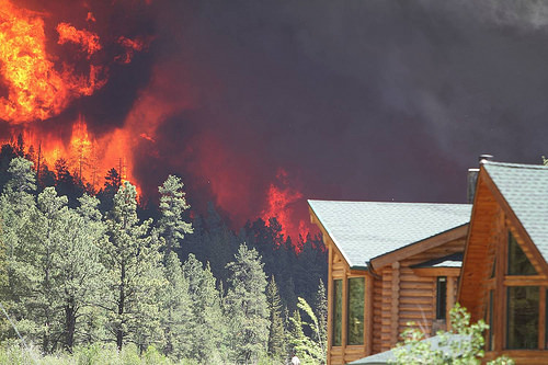 A photo of A house threatened by a forest fire in central Oregon.