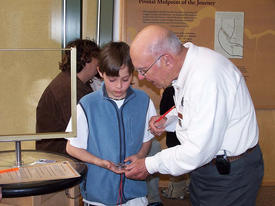 A photo of volunteer Jim Meade teaching a young boy how to string poles.