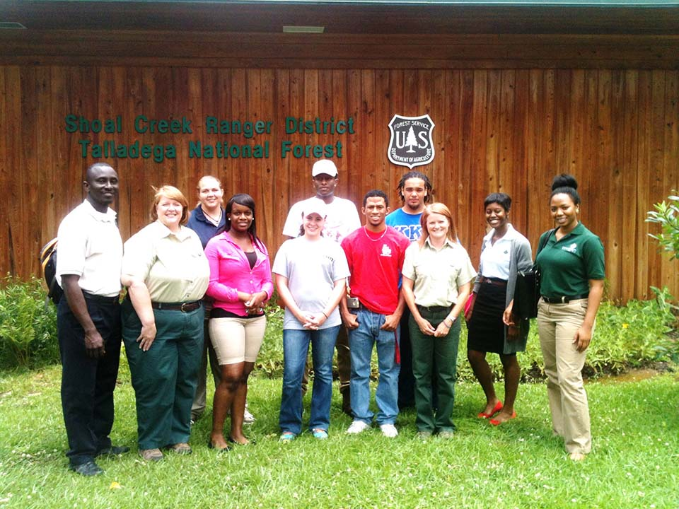 "A photo of Greening Youth Foundation staff standing with Forest Service staff and program participants in front a building that says,"" Shoal Creek Ranger District Talladega National Forest.\"""