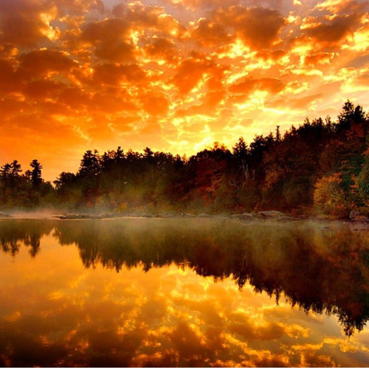 Sunrise or sunset with a clear reflection of the clouds and sky on a lake in the foreground.