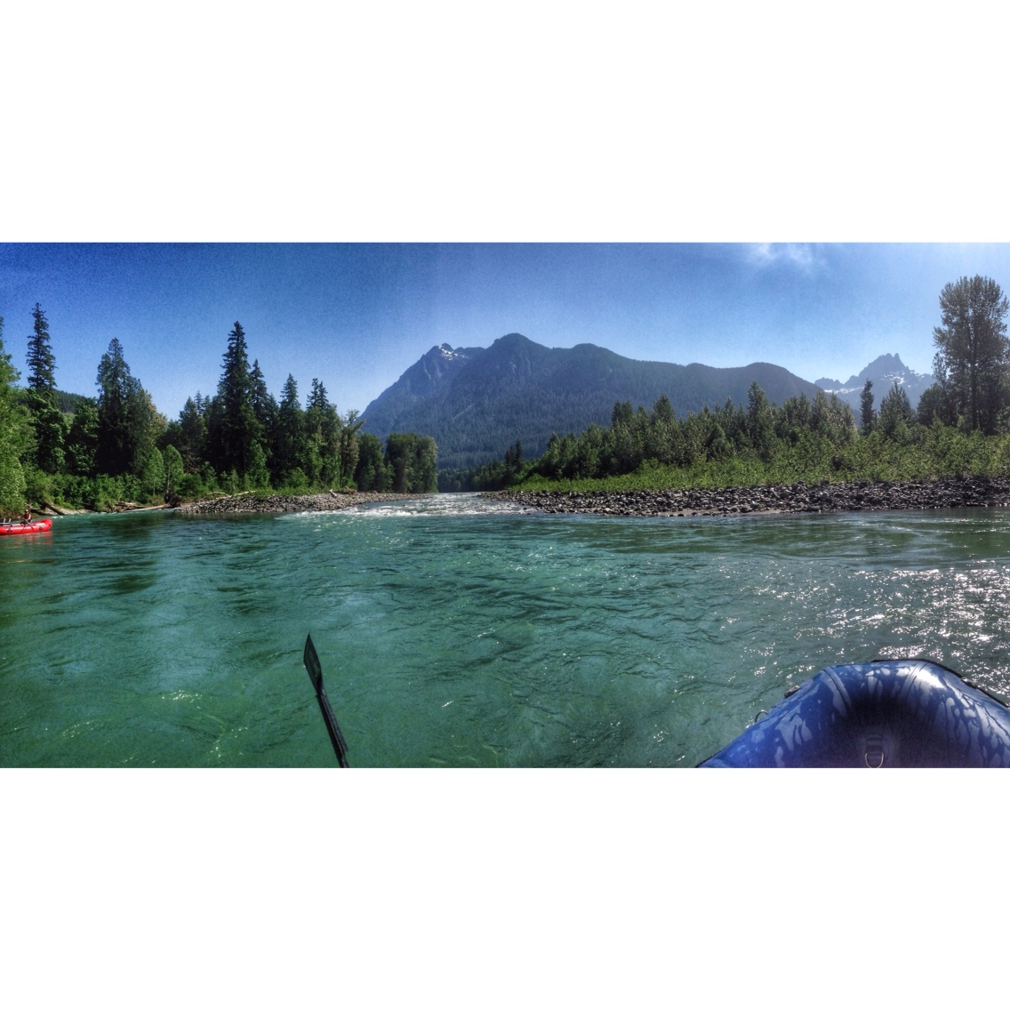 Pictures shows the front of a raft heading down the Sauk River with a group of mountains in the background.