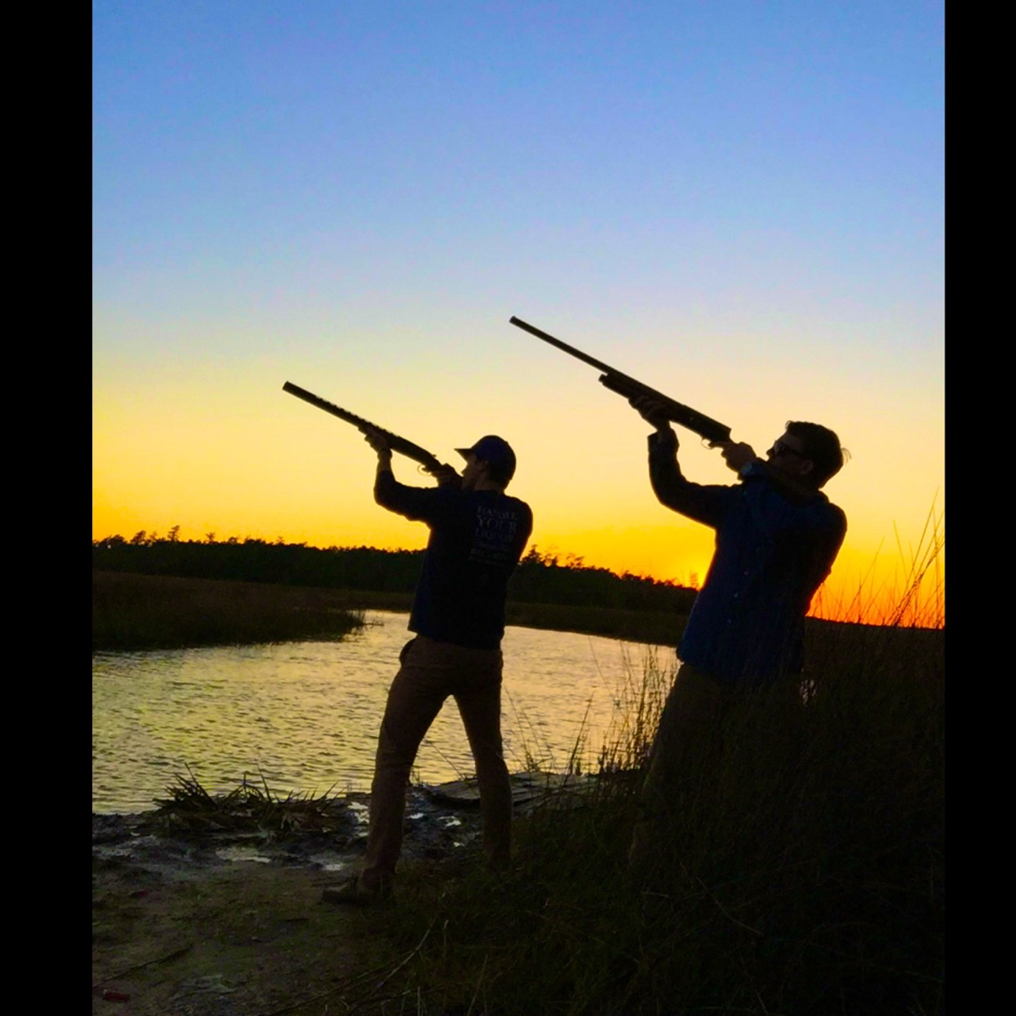 A picture of two hunders pointing their guns up towards the sky.