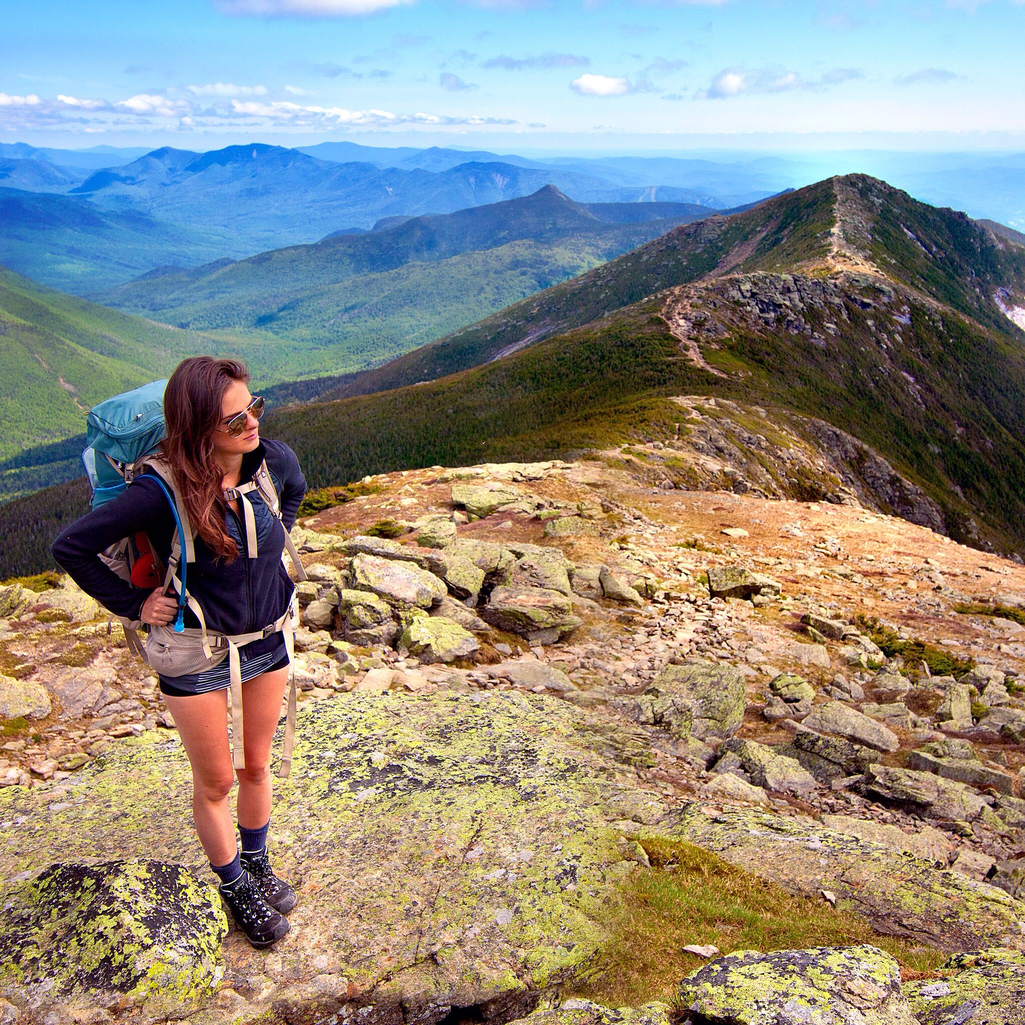 A picture of a female hiker on top of a scenic vantage point overlooking an endless view of mountains.